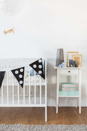 nightstand: White crib and nightstand in baby room