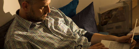 aloneness: Mature man browsing internet on laptop in bed Stock Photo