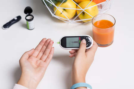 measuring: Woman with glucometer measuring blood sugar value Stock Photo