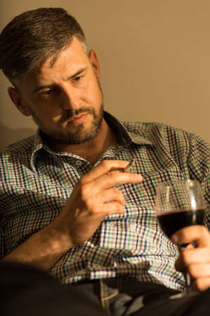 wistful: Mature man contemplating with cigarette and wine