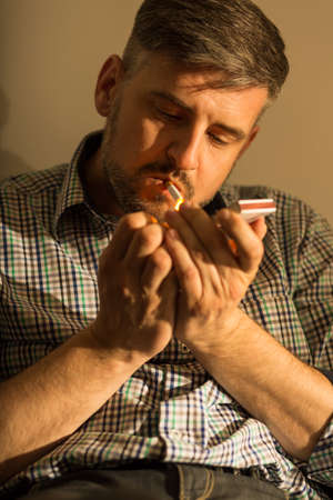 hooked up: Man lighting up a cigarette with a match