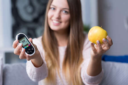 glucometer: Young diabetic woman holding glucometer and apple