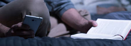 rest: Close-up of man with book writing massage on phone Stock Photo