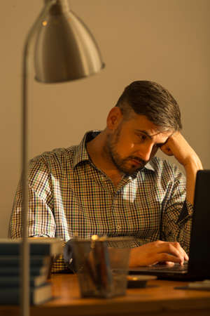 discouraged: Exhausted working man with laptop at home Stock Photo