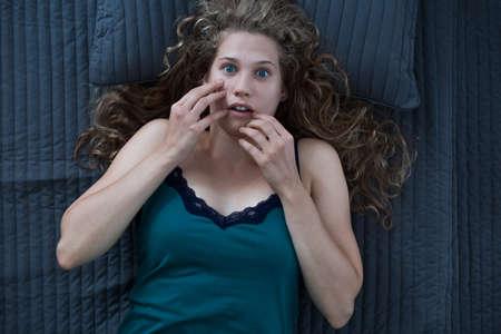침대에 악몽을 꾸는 무서워하는 여자