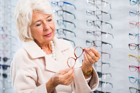 defect: Photo of lady with sight defect buying new frames Stock Photo