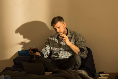 fag: Smoking man sitting on bed with laptop
