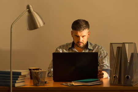 telecommute: Mature man working with laptop at home