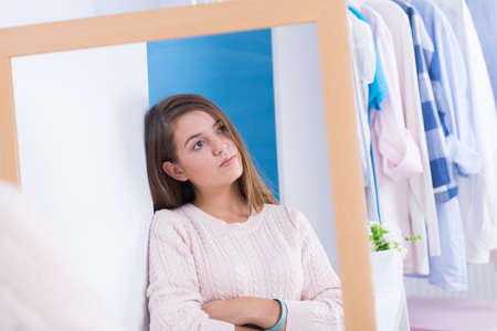 sad lady: Worried teen girl standing in front of mirror