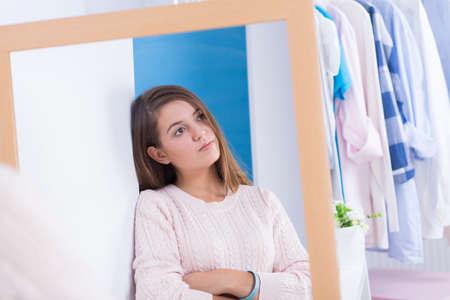 girl shirt: Worried teen girl standing in front of mirror