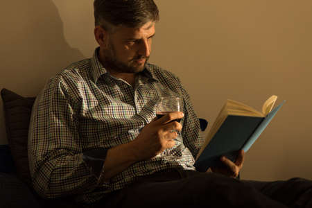 pleasure of reading: Man reading book and drinking wine in bed