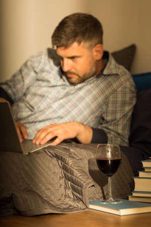 tomando vino: El hombre en el chat en Internet y bebiendo vino Foto de archivo