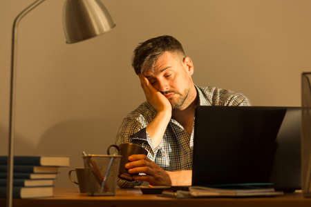 h: Exhausted man falling asleep while working at home