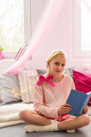 schoolgirl: Girl with book sitting on the bed