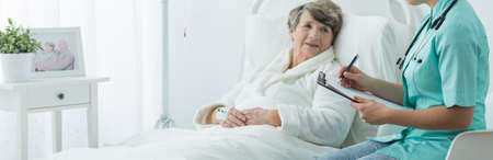 woman in bed: Older sick woman in hospital bed and her nurse Stock Photo