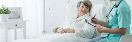 mujer en la cama: Una más vieja mujer enferma en la cama del hospital y su enfermera Foto de archivo