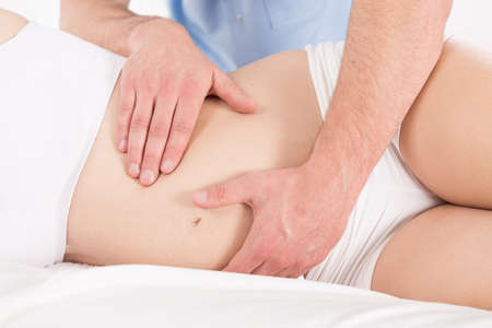 Close-up of therapeutic massage of pregnant womans belly Stock Photo