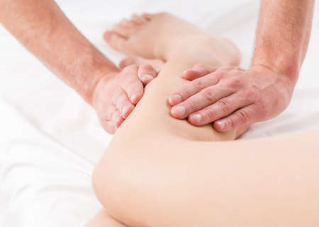 lymphatic drainage therapy: Close-up of male physiotherapist doing legs massage Stock Photo