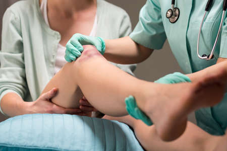 contusion: Woman with knee contusion receiving medical care