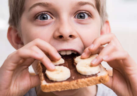 fruit eater: Image of boy eating sandwich with chocolate cream and banana