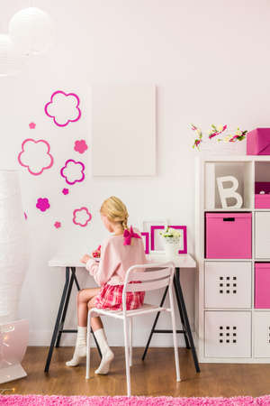 tarea escolar: Niña rubia sentada en el escritorio Foto de archivo