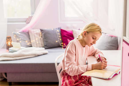 diaries: Little girl sitting at the desk and writing diary