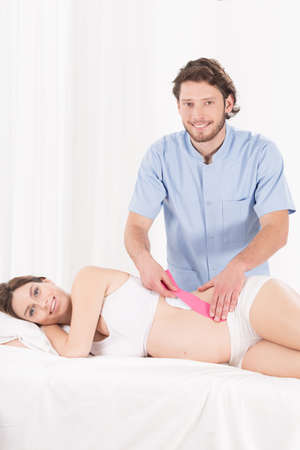 color therapist: Physiotherapist doing kinesiotaping on pregnant womans belly