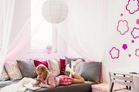 침대에서 책을 읽고있는 어린 소녀 스톡 콘텐츠