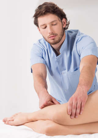 male body: Young male physical therapist at work in his office