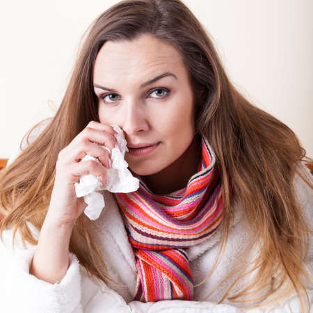 running nose: Ill woman lying in bed with tissue