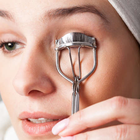 curler: Woman using curler to have beautiful eyelashes Stock Photo