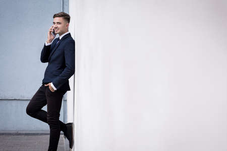 young businessman: Young businessman is leaning against white wall