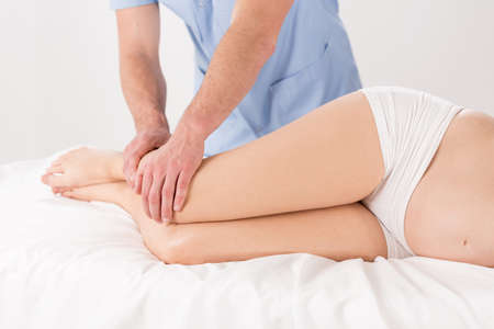 lymphatic drainage therapy: Physical therapist doing pregnant womans legs massage