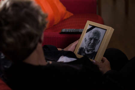 dearly: Portrait of elderly widow mourning dead close person