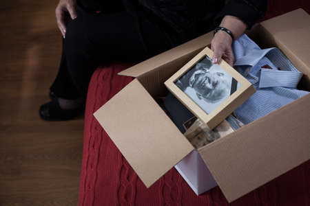 Photo of widow packing things of husband into box
