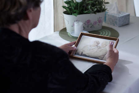 Picture of lonely aged female holding photo from past 版權商用圖片 - 50658937