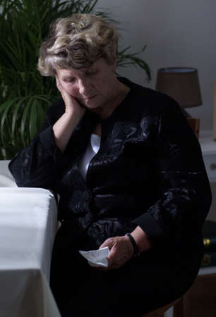 dearly: Image of elderly sad widow crying after funeral