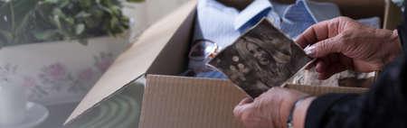 deceased: Banner view of beraved female packing things of deceased
