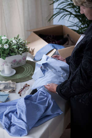 reminisce: Picture of miserable senior widow packing things of her husband Stock Photo