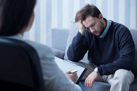 therapist: Photo of despair man during therapy with psychiatrist Stock Photo
