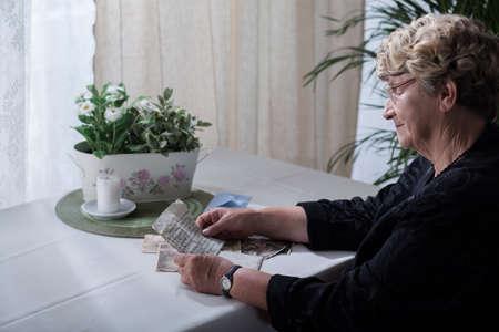 widow: Picture of smiling widow looking over memorabilia of her husband