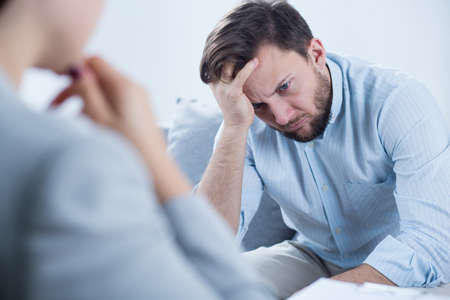 therapy room: Photo of man with depression talking with counselor Stock Photo