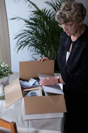 widow: Picture of sad bereaved female sorting things after late husband