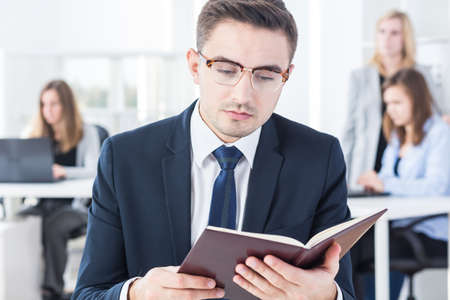 color consultant: Busy young businessman reading notebook at work