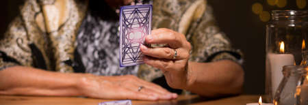 enchantment: Old fortune teller is looking at tarot