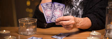 spiritualist: Old fortune teller is choosing cards  for a client Stock Photo