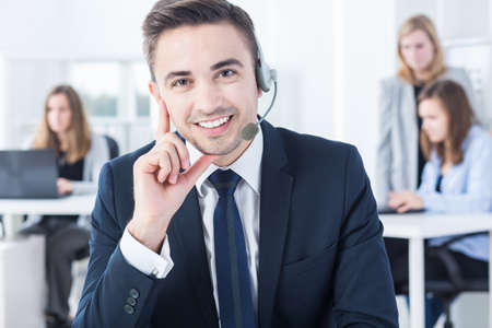 headset business: Handsome young male telemarketer with headset in office