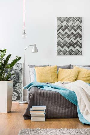 黄色のクッションとベッドの上のグレーのベッドカバー