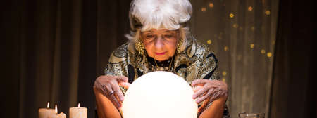 spirit medium: Old fortune teller is looking at crystal ball Stock Photo