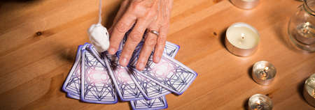 clairvoyant: Old fortune teller is predicting future from tarot